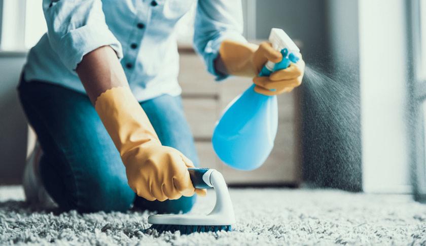 ung kvinna rengör en matta